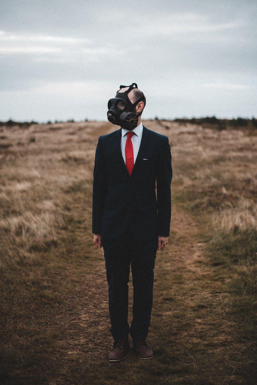 man in gas mask standing in field